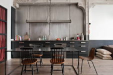 22 a black industrial kitchen made bolder with a concrete wall and metal countertops, handles and lamps