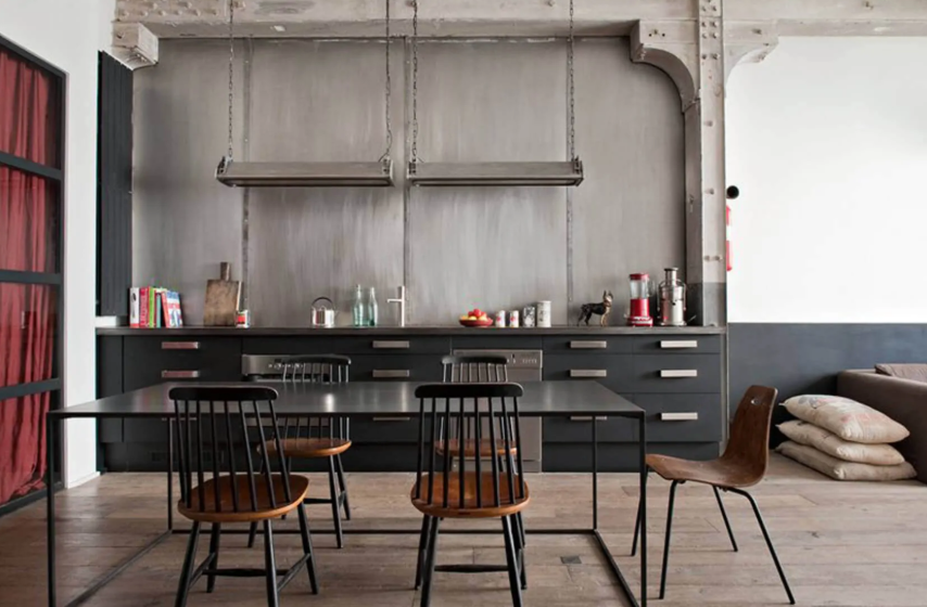 a black industrial kitchen made bolder with a concrete wall and metal countertops, handles and lamps