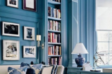 23 a bright blue home office and library with built-in bookshelves and elegant white furniture and artworks