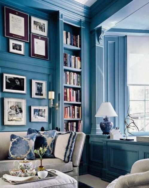 a bright blue home office and library with built in bookshelves and elegant white furniture and artworks