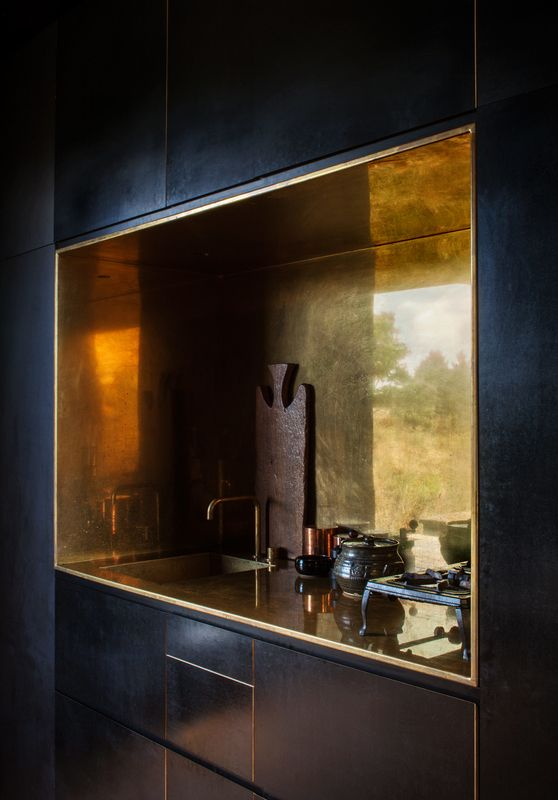 an elegant black kitchen with a gold backsplash niche looks very bold and very unusual