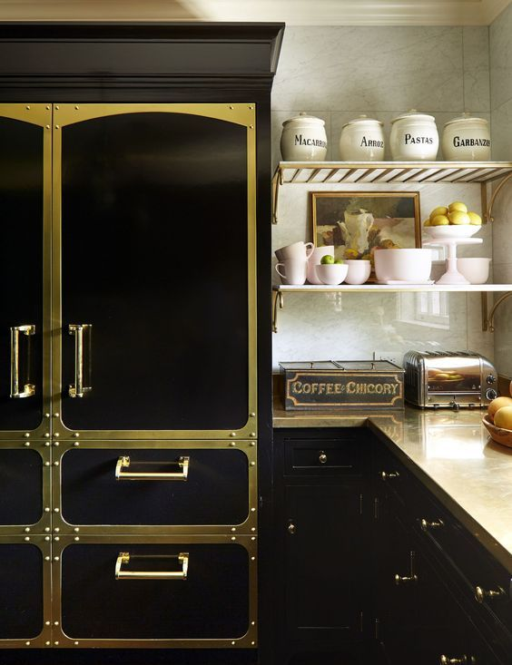 a creative and bold black kitchen spruced up with gold elements and matching metal countertops looks super glam