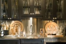25 a vintage-inspired black kitchen with a metallic backsplash, coutnertops and appliances looks very bold
