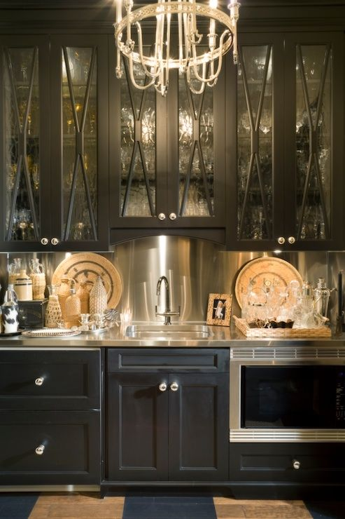 a vintage inspired black kitchen with a metallic backsplash, coutnertops and appliances looks very bold