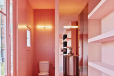 25 a whimsy bathroom done in salmon pink, with built-in shelves and windows to floof the space with natural light