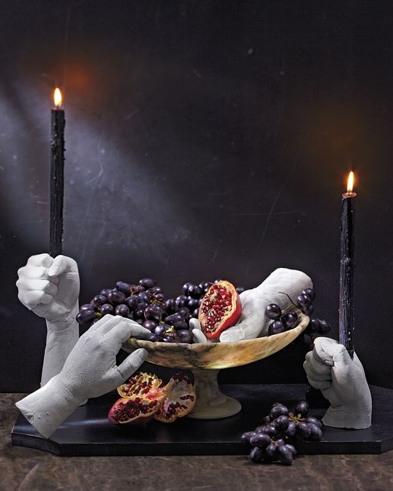 scary faux human hand candleholders with tall black candles and a bowl with fruits and matching hands