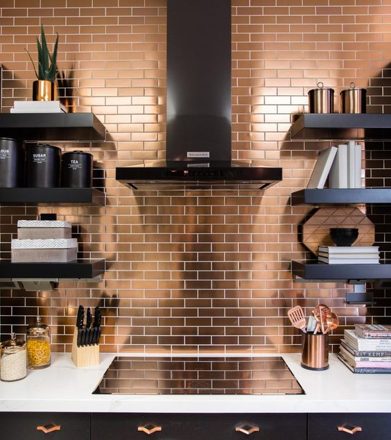 a modern black kitchen with a white countertop and a copper tile backsplash for a bright and shiny accent