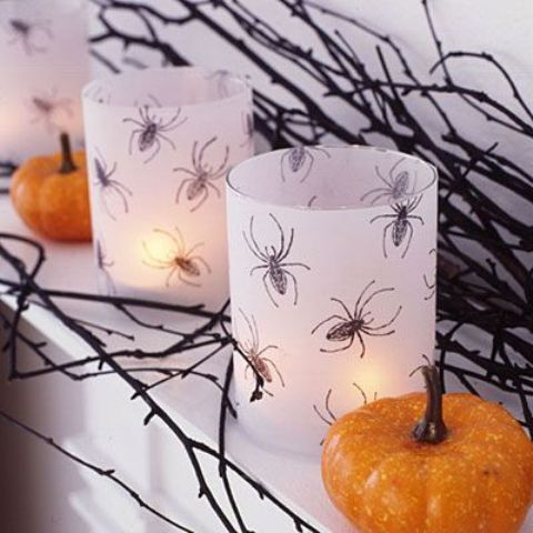 white candleholders with spiders drawn are a chic and simple DIY idea for Halloween decor