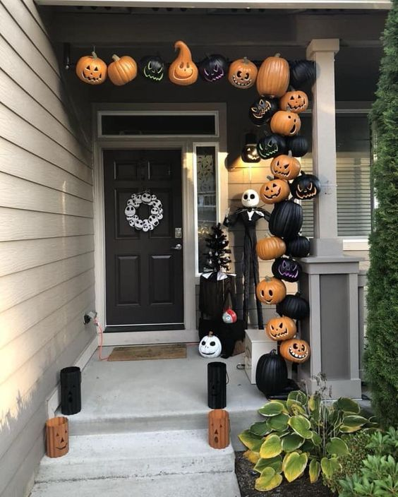 Nightmare Before Christmas porch with carved black and orange pumpkins, Jack Skellington and candle lanterns