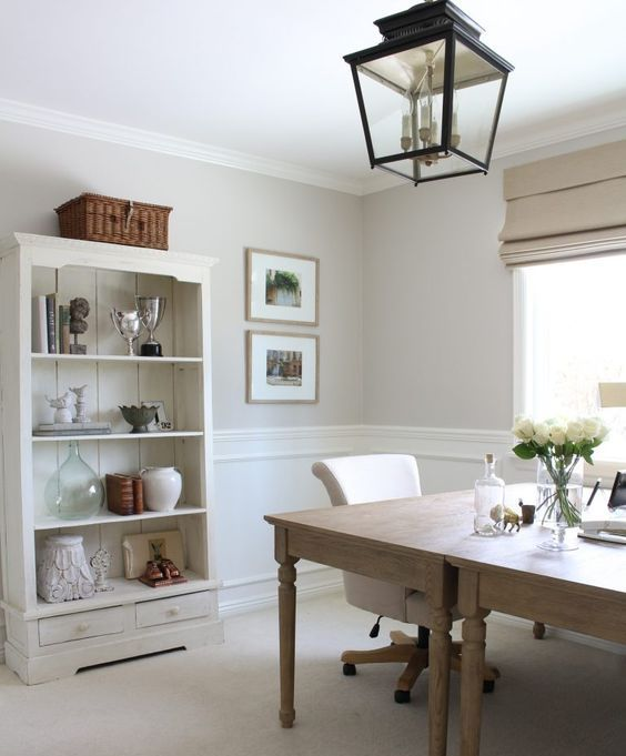a French-inspired home office with two wooden desks, a neutral buffet for storage and a blakc metal pendant lamp