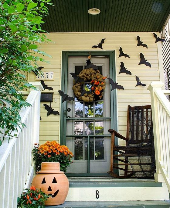 a Halloween porch with black bats on the walls, a mesh wreath, orange blooms, a carved pumpkin lantern