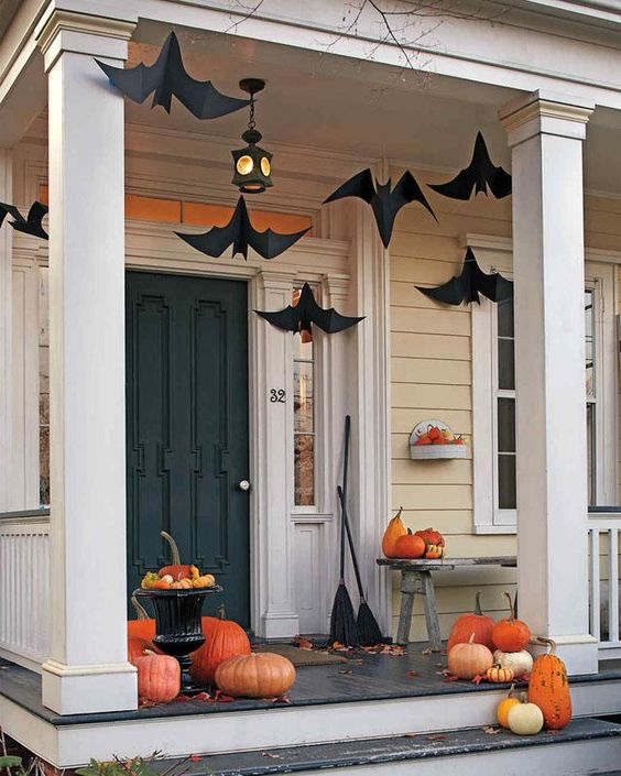 a Halloween porch with paper bats, natural orange pumpkins, brooms and fall leaves is a simple and cool idea