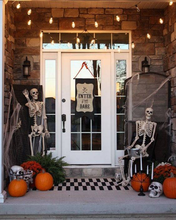 a Halloween porch with skeletons, spderwebs, orange pumpkins, skulls and candles plus a sign