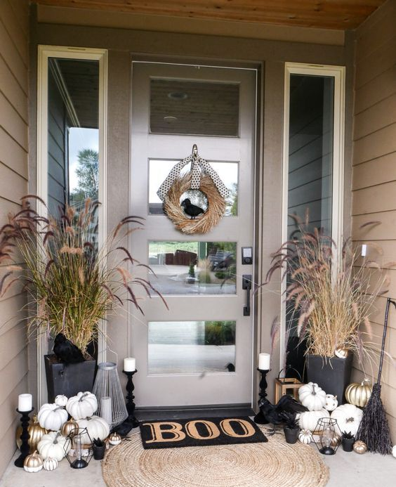 a Halloween porch with white and gilded pumpkins, candles, brooms, dried herbs and a wreath of wheat