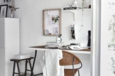 a Mordic neutral home office with a trestle desk, some wall-mounted shelves, a blakc stool and a woven rug