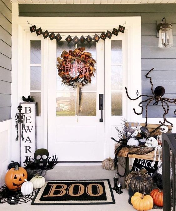a black and white Halloween porch with a bright wreath, a black bunting, skeletons and skulls, natural and faux pumpkins