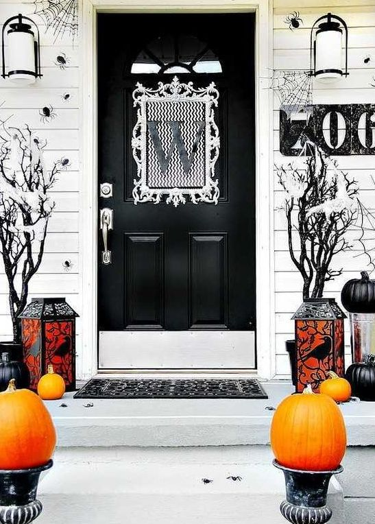 a black and white Halloween porch with orange and black pumpkins, candle lanterns and black trees plus spiders