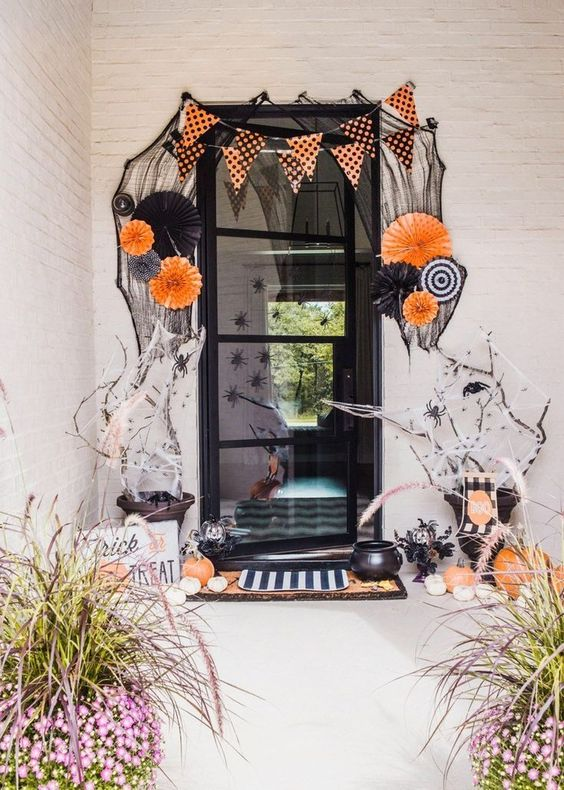 a bold and whimsical Halloween porch with paper fans, buntings, orange and white pumpkins, spiders and branches