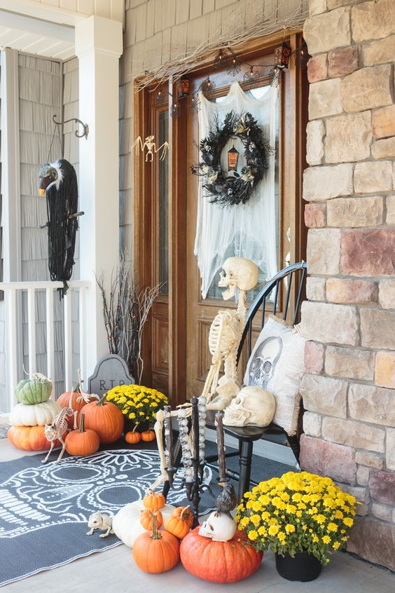 a bright Halloween porch with a black feather wreath, a skeleton and skulls, bright fall blooms and natural pumpkins