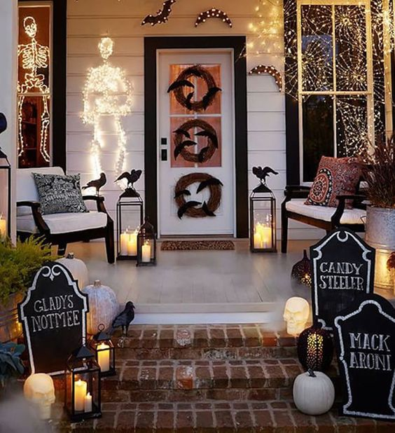 a bright Halloween porch with white pumpkins, candle lanterns, fake blackbirds, chalkboard signs, lights, skeletons and wreaths