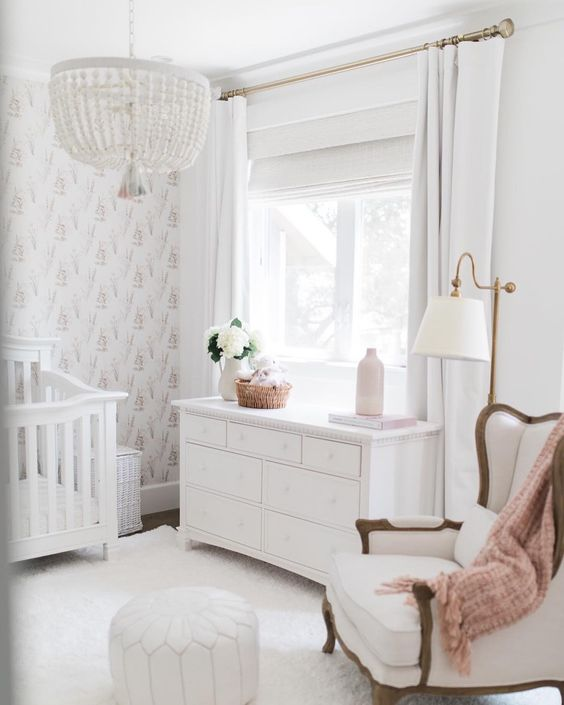 a chic neutral nursery with a bead chandelier, a vintage chair and crib, a dresser, white rugs and a Moroccan pouf