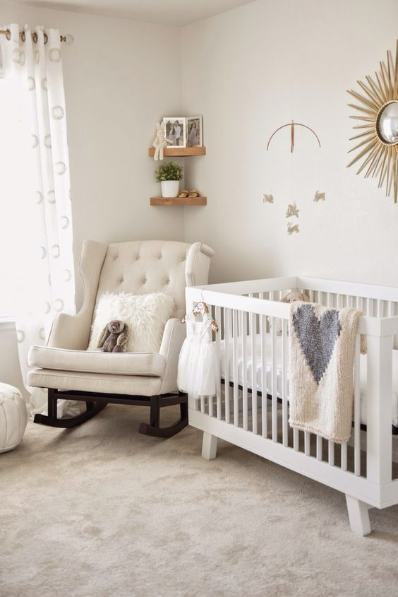 a chic neutral nursery with a rocker chair, a simple crib, a sunburst artwork, corner shelves and printed textiles
