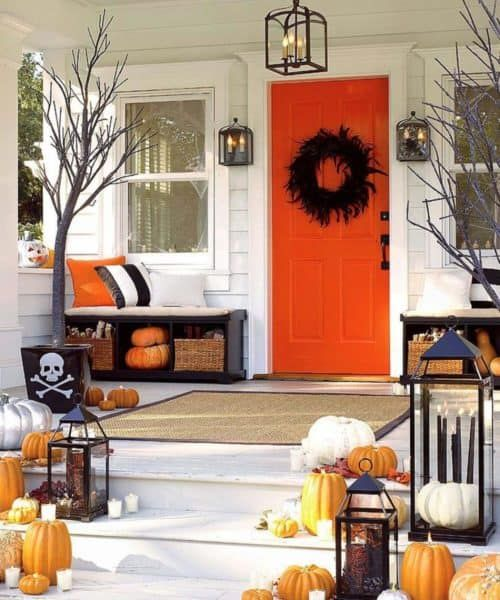 a colorful Halloween porch with a black feather wreath, orange and white pumpkins, candle lanterns and colorful and striped pillows