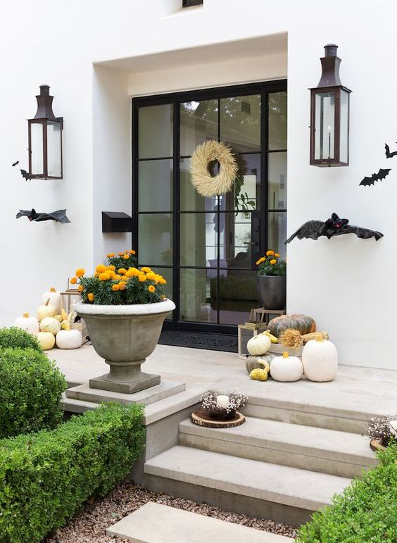 a contemporary Halloween porch with black bats, heirloom pumpkins, bold blooms and a wheat wreath