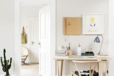 a cozy neutral home office with some wooden furniture, art on the wall and a cactus in a pot