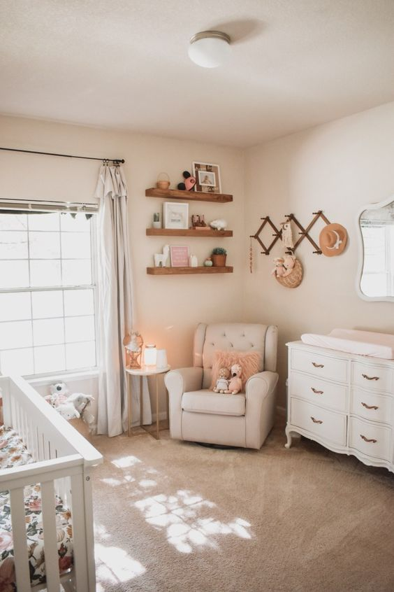 a cozy neutral nursery done with floating shelves, neutral curtains, vintage furniture, a cozy rug and some woven elements