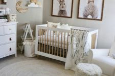 a cozy neutral nursery with artworks, a crib, layered rugs, a fringe stool and some simple wooden furniture