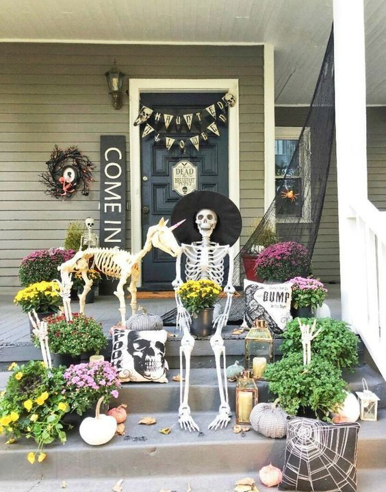 a creative Hallowene porch with a skeleton and a skeleton dog, candle lanterns, blooms and greenery and signs and buntings