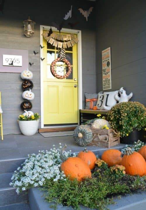 a cute and colorful Halloween porch with greenery, blooms, natural pumpkins, a ghost pillow, a buting, a wreath and a stack of pumpkins