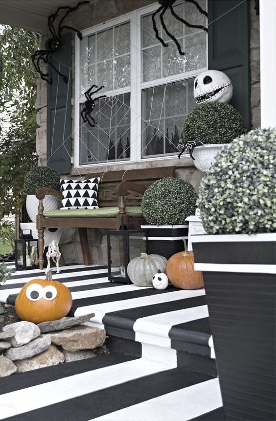 a fun black and white Halloween porch with a striped floor, natural pumpkins with faces, greenery, a spiderweb with spiders