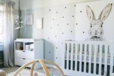 a fun neutral nursery with a creative wall, white modern furniture, a printed rug, a beaded chandelier and baskets for storage