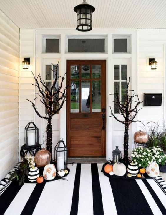 a gorgeous Halloween porch with painted and stenciled pumpkins, fall blooms in pots, black trees with lights and a large striped rug