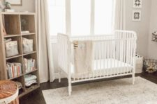 a light-filled neutral nursery with a crib, a wooden shelving unit, a printed rug, baskets and neutral curtains