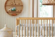 a mid-century modern nursery in neutrals, with wooden furniture, a basket and a round shelf