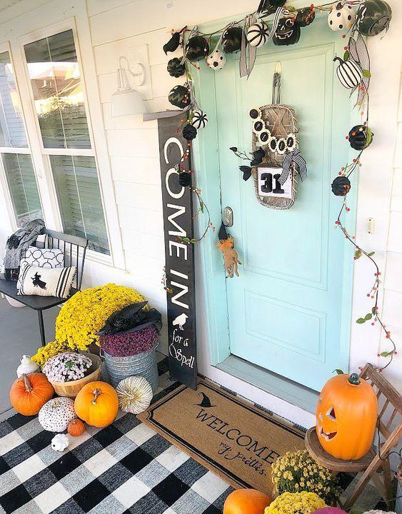 a mini black and white pumpkin garland, bright fall blooms in baskets, bright pumpkins and a plaid mat