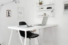 a minimalist white workspace with a white desk, a shelving unit, artworks and a little stool by the desk
