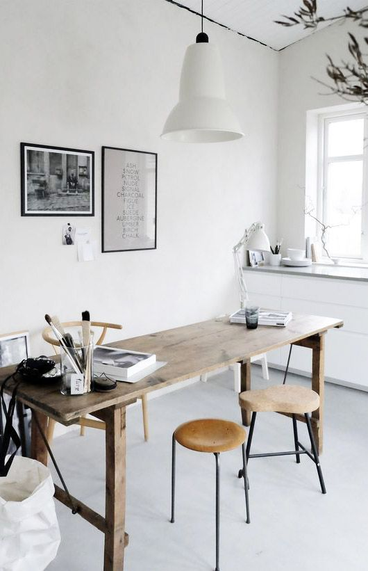 a neutral Scandinavian home office with a wooden desk, wooden and cork stools, a pendant lamp and some black and white art