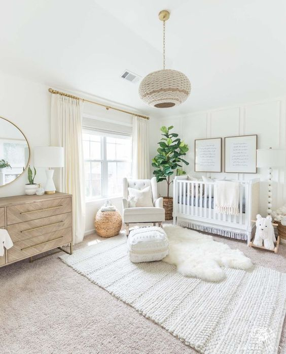 a neutral and fresh nursery with layered rugs, a woven lamp, a crib, a wooden dresser and a tree in a basket pot