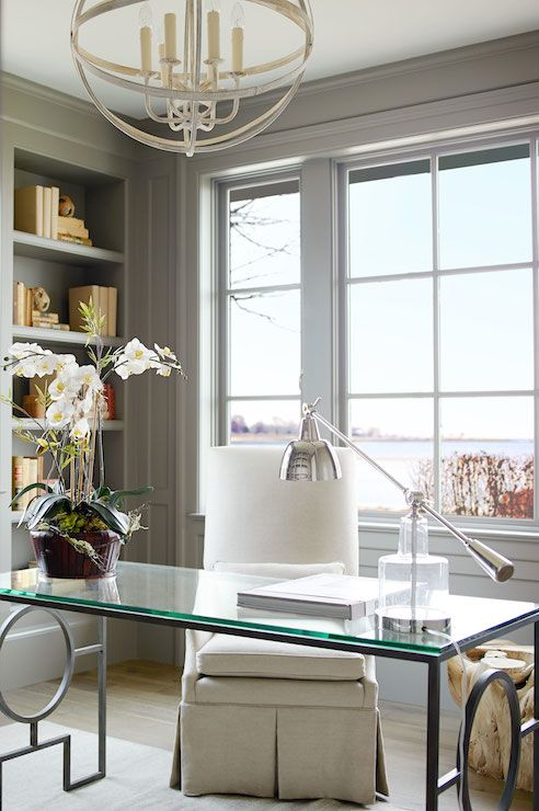 a neutral and super elegant home office in light grey, a glass desk, a white chair, a farmhouse chandelier and a cool view