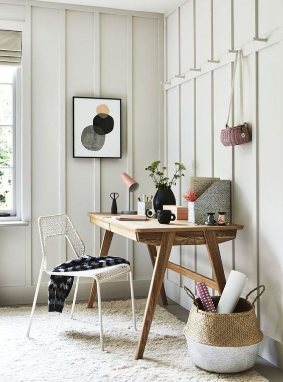 a neutral and welcoming home office with a wooden desk, a basket, a wire chair and some bright stuff on the desk