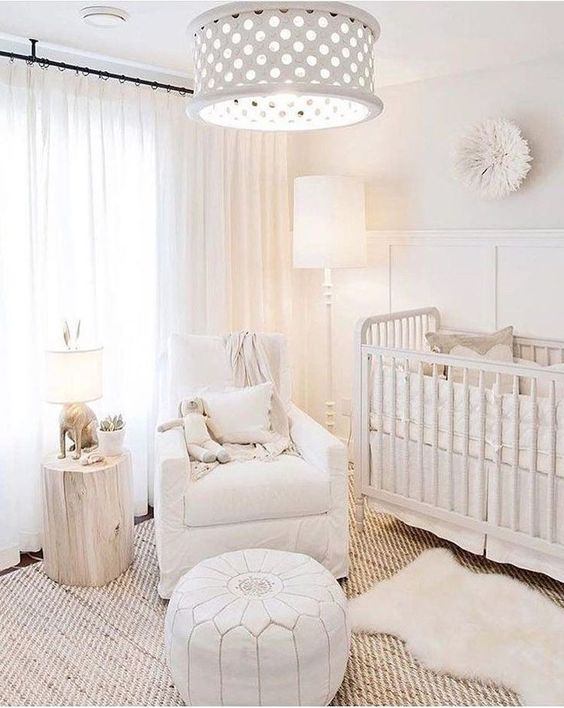 a neutral baby nursery with a jute rug, a white Moroccan pouf, a tree stump, a perforated lamp and a vintage crib
