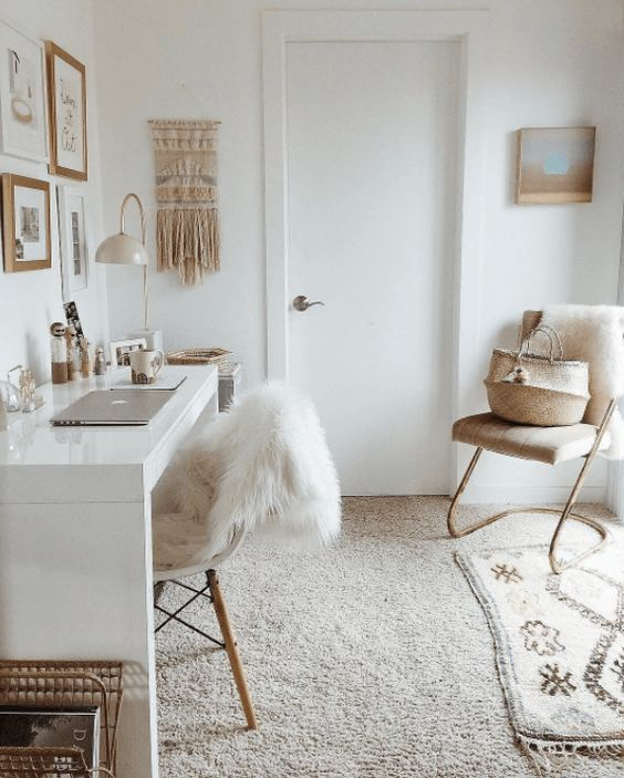 a neutral boho home office with a gallery wall, a white desk, layered rugs and a macrame hanging looks relaxing