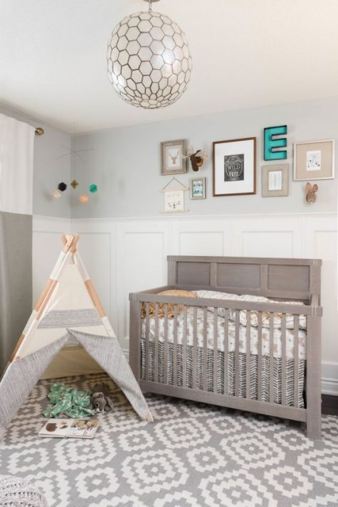 a neutral boho nursery done in greys and pastels, with a printed rug, a grey crib and a teepee