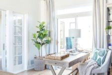 a neutral farmhouse home office with a wooden trestle desk, a white chair, wooden bead chandeliers, touches of blue and striped curtains