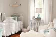 a neutral farmhouse nursery spruced up with mint touches, a printed rug, a fur ottoman, cozy vintage furniture