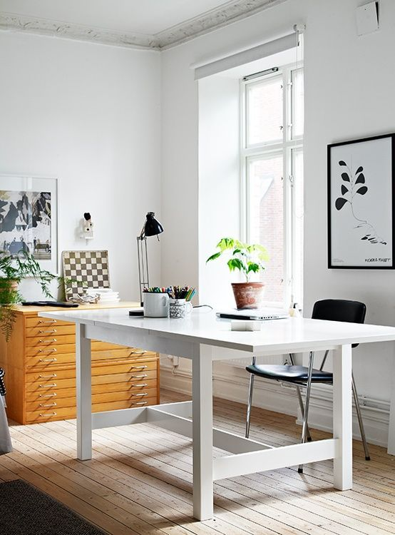 a neutral modern home office with a white desk, a wooden cabinet, some black and white art and a black chair